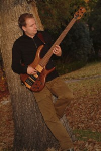 Robin playing bass by tree